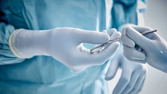 Surgeons in the operating room removing gowns